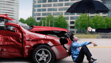 Young businessman sitting under umbrella in front of a damaged car after collision